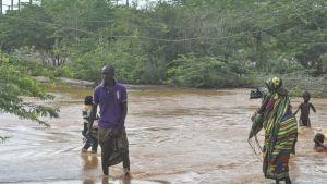 Mies, nainen ja lapsia kävelee tulvavedessä.