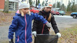 Miisa Liukkonen ja Viivi Kauhanen keräävät roskia koulun lähiympäristössä.