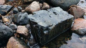 Suorakaiteen muotoinen tyynylaava kivi. ympärillä osittain vedessä jääkauden pyöristämiä rantakiviä.