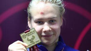 Petra Olli posereaa EM-kultamitalin kanssa.