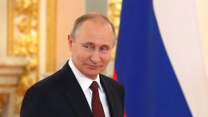 Putin katsoo hieman vasemmalle vienosti hymyillen. Hänellä on yllään tumma puku, valkoinen kauluspaita ja viininpunainen kravatti. Taustalla näkyy Venäjän lippu ja Kremlin kullanhohtoista salia.