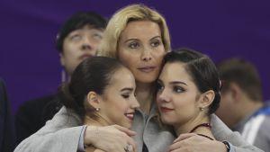 Alina Zagitova (vas.) juhli Pyoengchangissa olympiakultaa. Valmentaja Eteri Tutberidzen kainalossa oikealla Jevgenia Medvedeva.