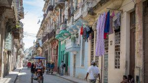 Kuva kadulta Havannasta. Kapealla kadulla ajaa pyörätaksi.