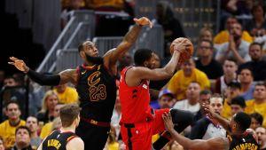 Toronton CJ Miles yrittää koria, Clevelandin LeBron James torjuntaa.