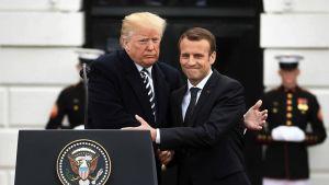 Donald Trump ja Emmanuel Macron syleilevät.