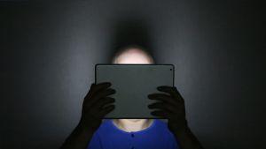 Mies katsoo tablettia pimeässä.