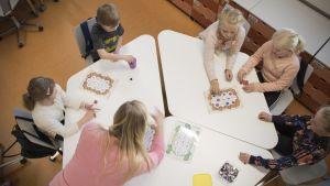 Ekaluokkalaisia pöydän ääressä pelaamassa.