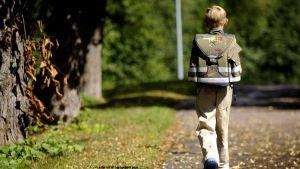 koulupoika kävelee reppu selässä
