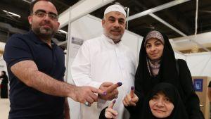 Kuvassa oikealla mustapaitainen mies, keskellä valkoasuinen mies ja vasemmalla mustiin pukeutunut nainen seisomassa ja toinen mustiin pukeutunut nainen istumassa. Ihmiset ovat käyneet äänestämässä Irakin vaaleissa Dubaissa. Kaikkien etusormet ovat musteessa äänestämisen merkiksi.