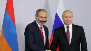 Pashinian ja Putin kättelevät Armenian ja Venäjän lippujen edessä.