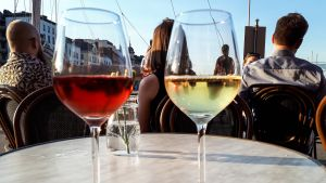 Viinilaseja terassin pöydällä, taustalla ihmisiä