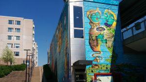 Myyrmäen asema. Seiniin maalattu katutaidetta. Rakennuksen edessä seisoo uuden paikallislehden Ari Martinaho.