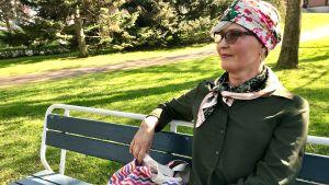 Nainen istuu puiston penkillä