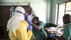 Vihreään pukeutunut sairaanhoitaja asettelee suojalaseja hoitajalle, joka on pukeutuneet täysin peittävään suojapukuun.