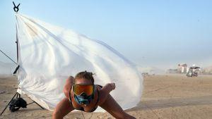 MidBurn -festivaali 2018 Negevin autiomaassa Israelissa. Nainen tanssii teknomusiikin soidessa laskettelulasit silmien edessä ja huivi suun edessä jottei hiekka pääse silmiin ja suuhun.
