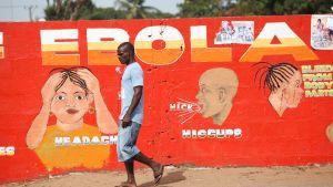 Mies kävelee ebolavalistustaulun edestä.