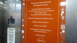 Hissin sisäseinässä oleva teksti, jossa kerrotaan Hämeenlinnan hitaimmasta hissistä