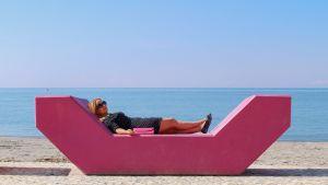 Tanja Honkanen makaamassa veistoksen päällä.