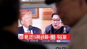 Eteläkorealaiset katsovat tv-lähetystä jossa näkyy Donald  Trump ja Kim Jong-Un.
