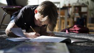 Poika tekee kotiläksyjä lattialla.