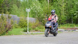 Nuori tyttö ajaa mopolla.