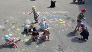 Lapset piirtävät asfalttiin