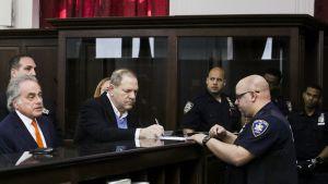 Harvey Weinstein allekirjoitti papereita oikeustalolla New Yorkissa perjantaina.