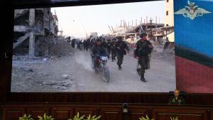 Venäläinen armeijan Sergei Rudskoi näytti kuvia venäläisistä sotilaista Syyriassa 23. toukokuuta Moskovassa.