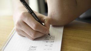 Nuori laskee matematiikan läksyjä.