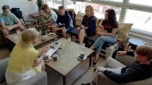 Kuhmon kaupunginjohtaja Tytti Määttä kahdeksasluokkalaisten kanssa kahvilan pöydän ääressä.
