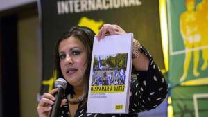 Ihmisoikeusjärjestön edustaja esittelee tuoretta raporttia kädessään.