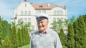 Kevään 2018 vanhin ylioppilas Matti Dahlbacka hymyilee Pietarsaaren lukion edessä ylioppilaslakki päässään.
