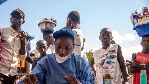 WHO:n kanssa työskentelevä sairaanhoitaja valmistautuu jakamaan rokotteita Kongon Mbandakassa.