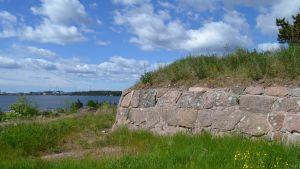 Fort Katariinan linnoituksen muuria, taustalla HaminaKotkan sataman Mussalon rakenteita.