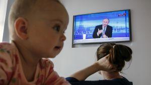 Venäläinen nainen seuraa vauvansa kanssa Presidentin suora linja -ohjelmaa.