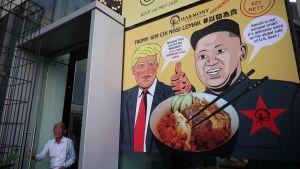Ravintolan mainosjuliste, jossa on piirroskuvat Trumpista ja Kimistä. Puhekuplissa piirroshahmot kehuvat ruokalajia.