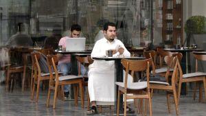 Mies istuu ravintolan terassilla.