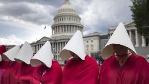 Handmaid's Tale -sarjan synnyttäjiksi pukeutuneet naiset osoittavat mieltään valkoisen talon edustalla Washingtonissa.