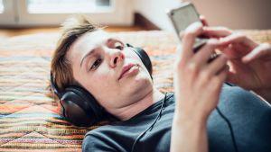 nuori nainen kuuntelee kuulokkeilla musiikkia