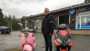 Polvijärven kunnanjohtaja Jari Tuononen seisoo kahden moposkootterin välissä.
