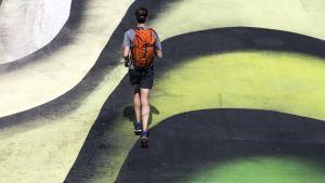 Juoksija juoksee katuun maalatun teoksen päällä.