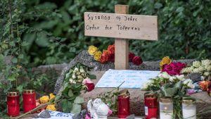 Raiskatun ja murhatun saksalaistytön muistokynttilöitä ja kukkia.