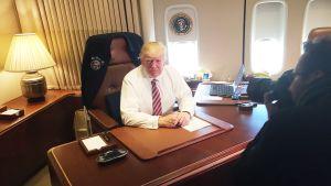 Donald Trump työpöytänsä ääressä Air Force One -lentokoneessa.