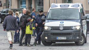 Poliisi kohta kansalaisia Turun torilla.