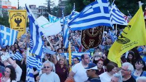 Mielenosoittajat heiluttavat Kreikan lippuja.