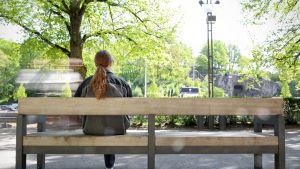 Nainen yksin puistonpenkillä.