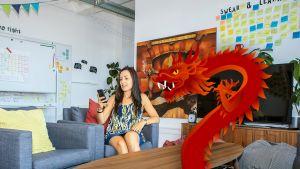 Nainen katsoo kännykkäänsä, kuvassa myös piirretty punainen lohikäärme.