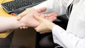 Lääkäri tutkii potilaan kättä.