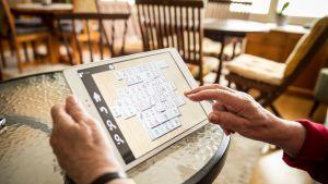Ikäihminen pelaa tabletilla tietokonepeliä.