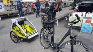 Sähköpyörän perässä oleva lasten kuljettamiseen tarkoitettu kärry.